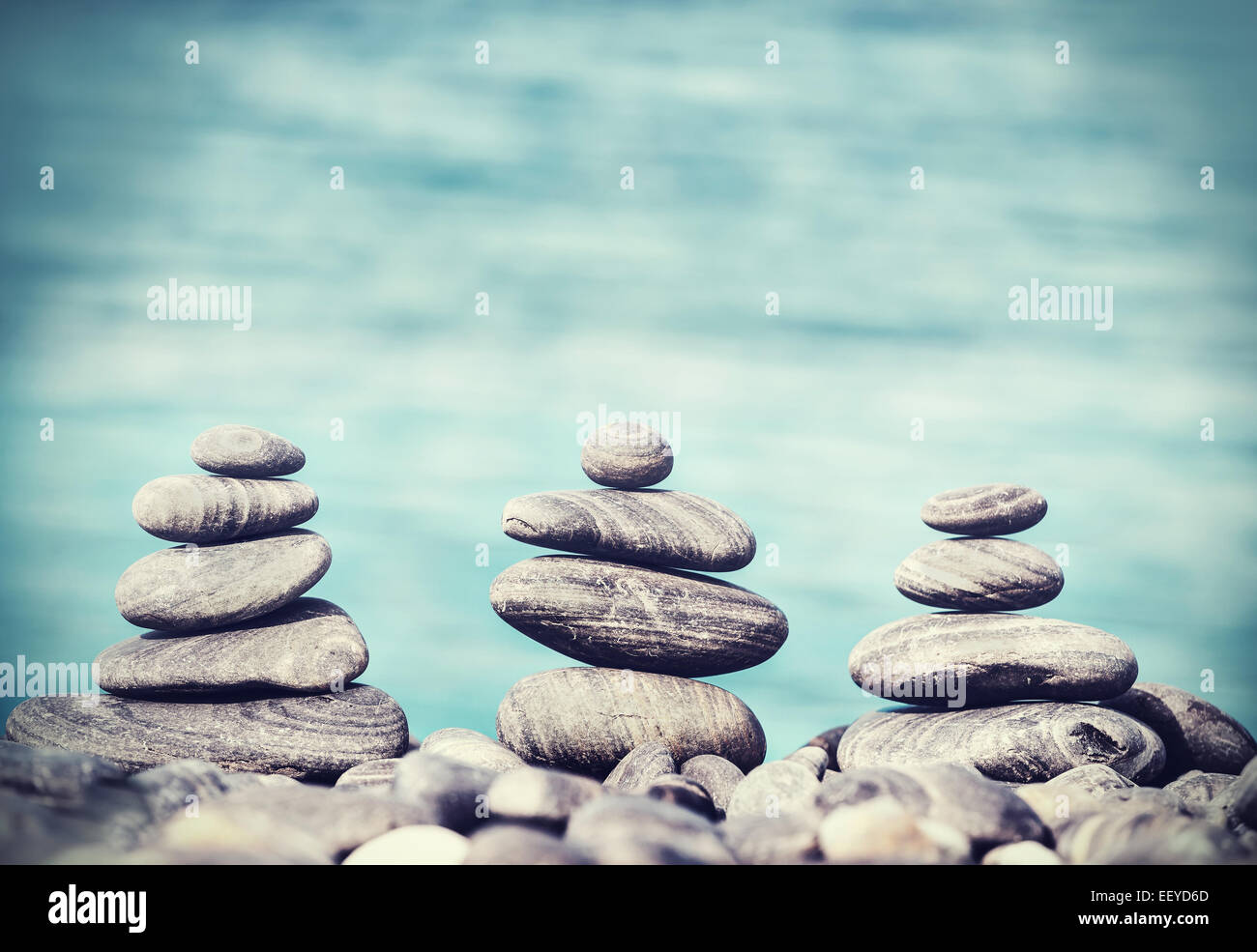 Vintage retro hipster style image of stones on beach, Zen spa concept background. - Stock Image