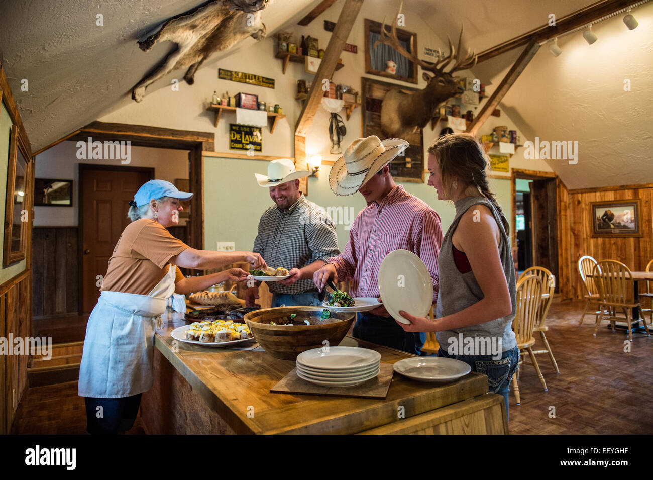 Gini Mc La Master serves Jake Rupp, Tanner Lee and Abigail Williams  inside their dining hall at the  Blacktail - Stock Image