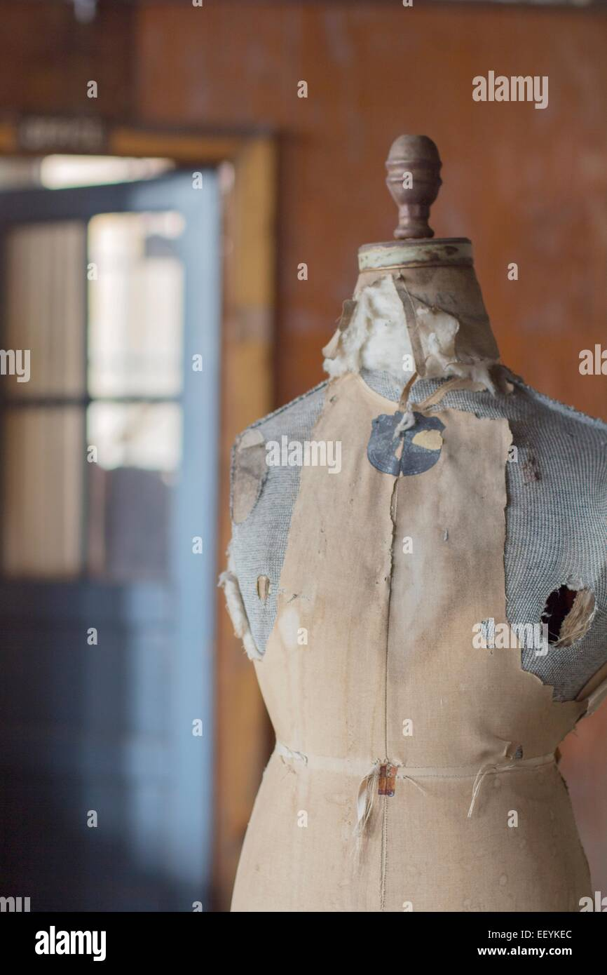 An old dress form mannequin in an abandoned clothing factory. - Stock Image