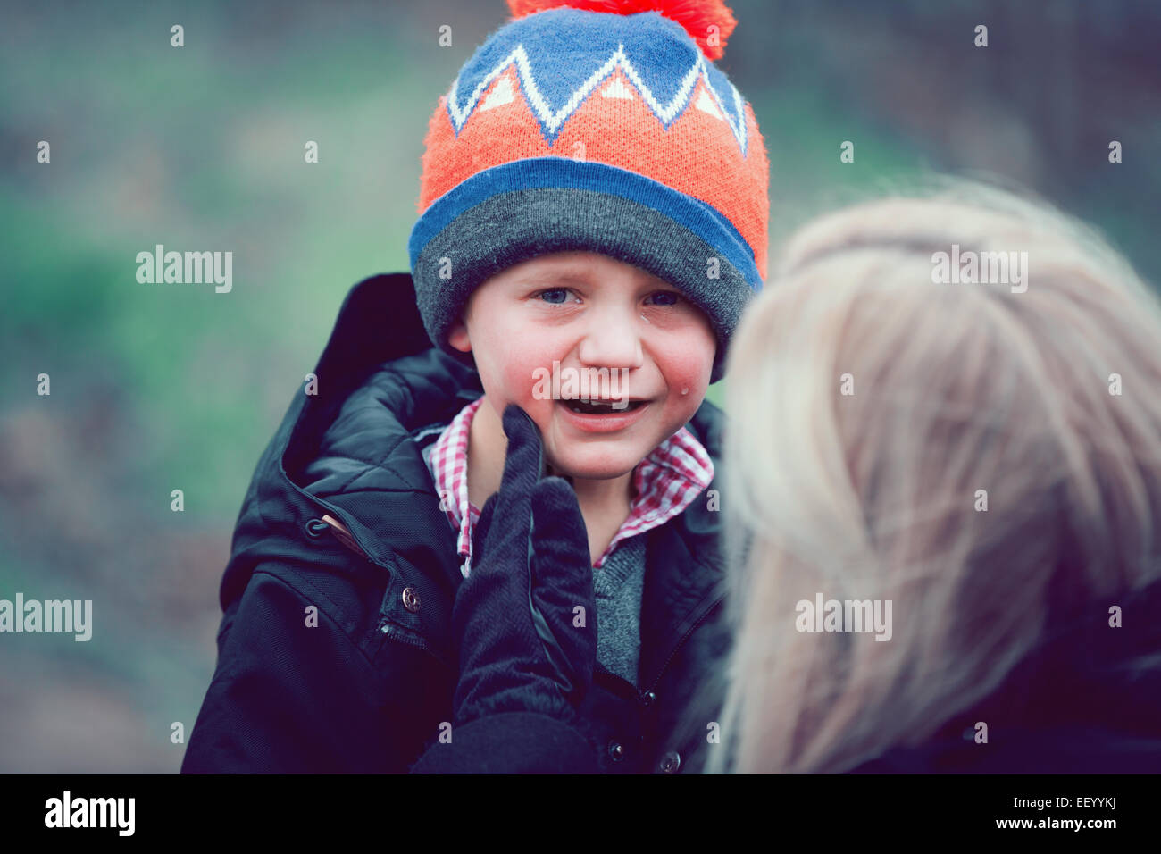young boy with mother upset crying - Stock Image