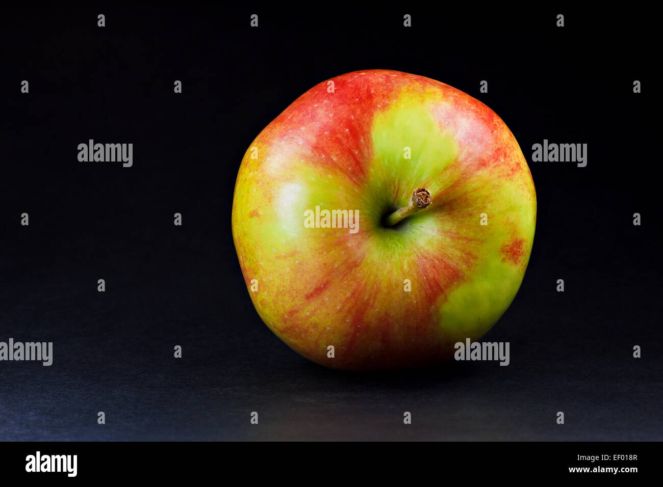 An apple on a black background. - Stock Image