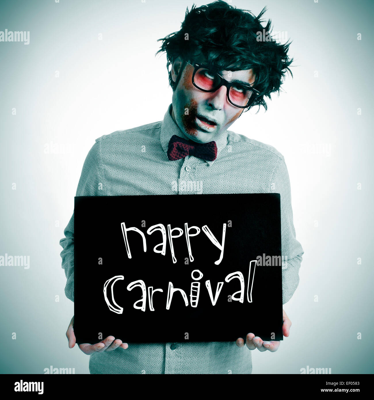 a man dressing a zombie costume with a black signboard with the text happy carnival written in it - Stock Image