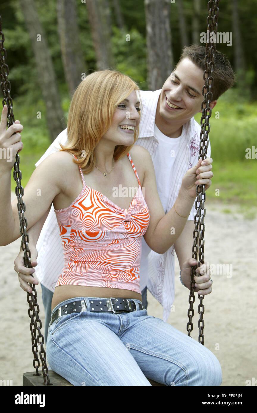Maedchen Mann Junge Flirt Liebe Freundschaft Zuneigung Schaukel Froehlich Lachen Freizeit Spielplatz Spielgeraete - Stock Image