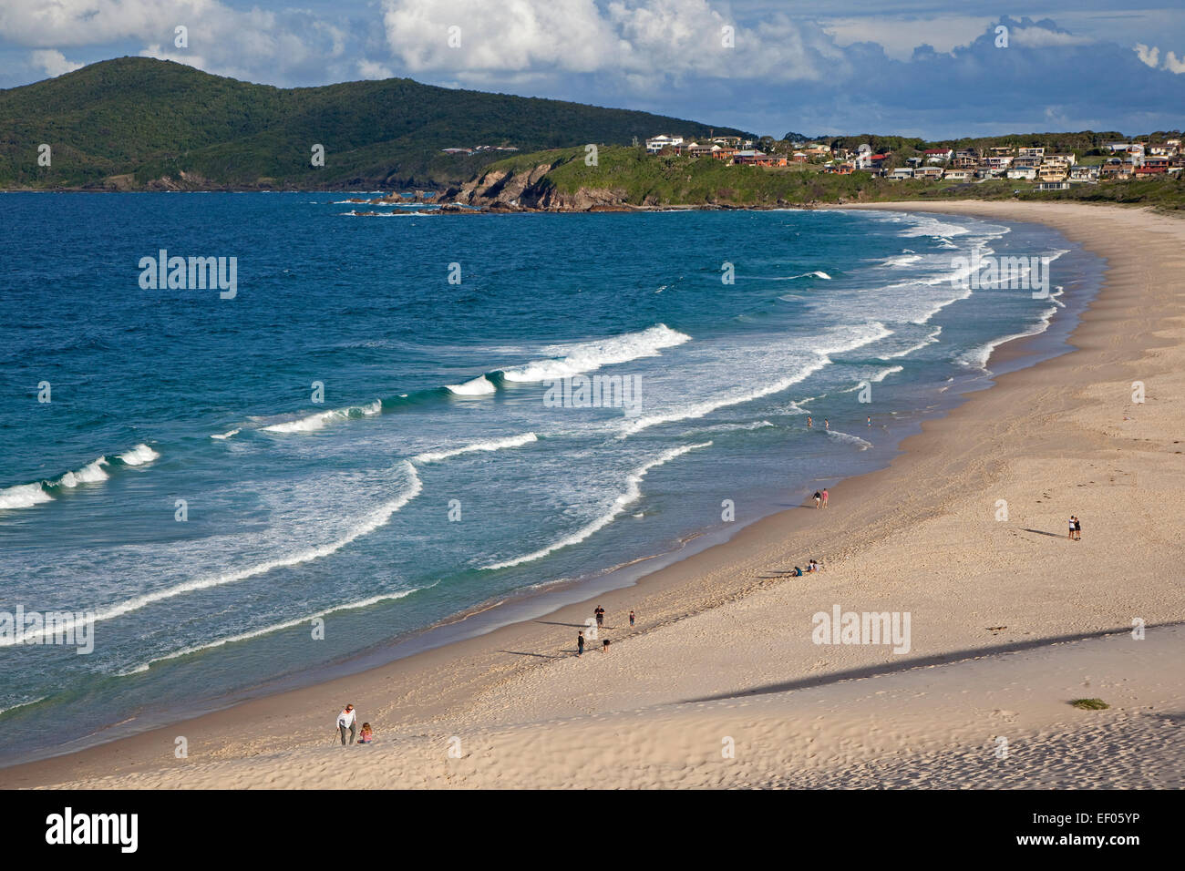Tourists walking along One Mile Beach at Forster along the  Tasman Sea, New South Wales, Australia - Stock Image