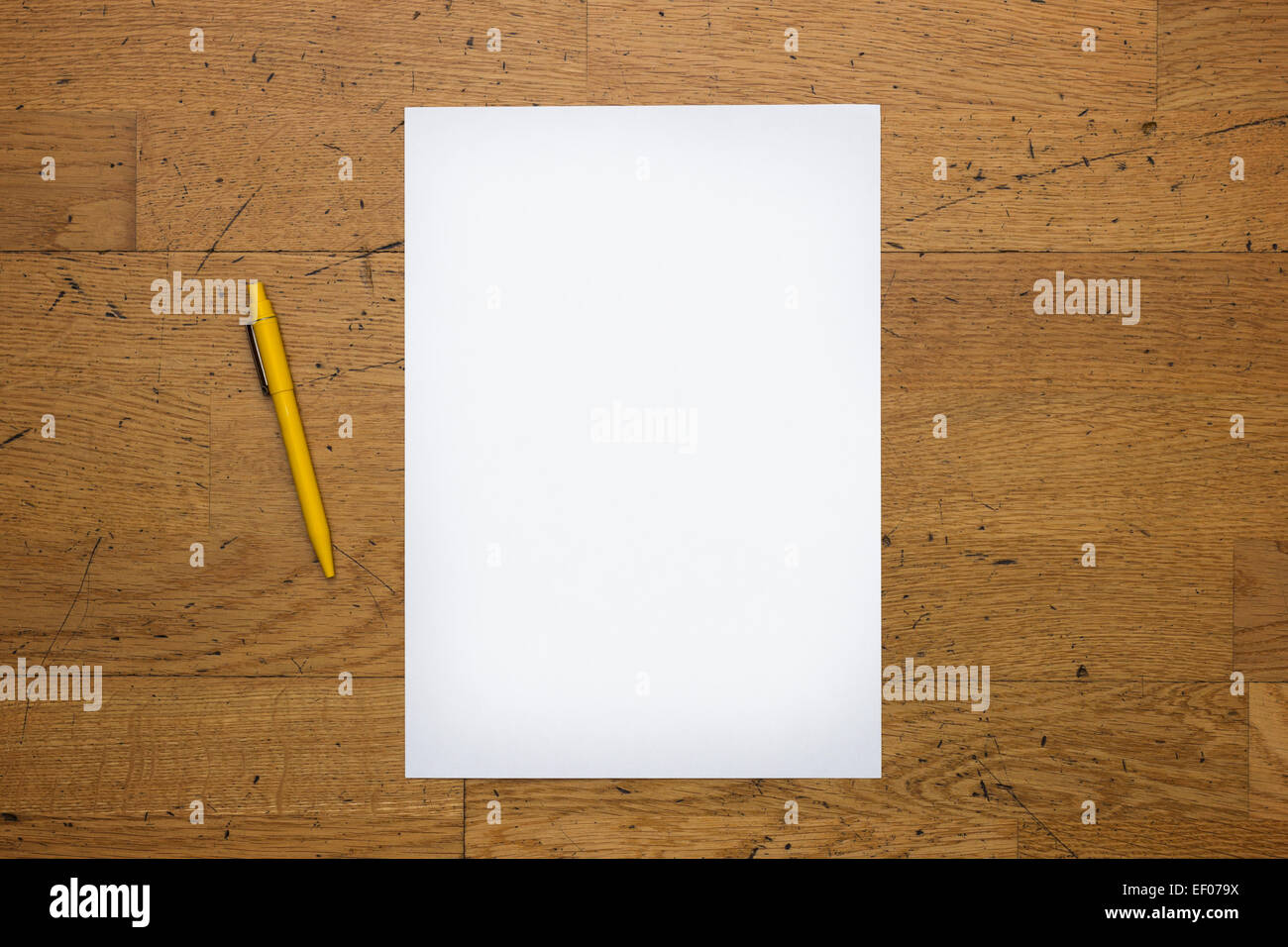 Pen and a blank white paper sheet on a worn wooden table surface, viewed from above - Stock Image
