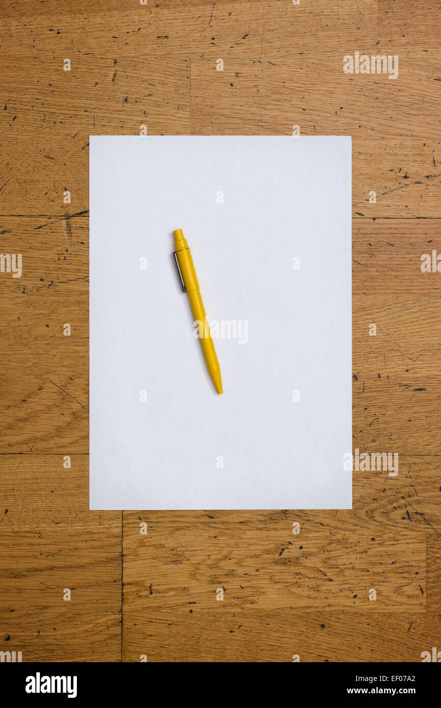 Pen on a blank white paper sheet on a worn wooden table surface, viewed from above - Stock Image