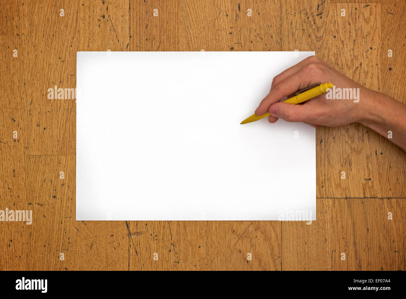 Hand holding pen on a blank white paper sheet (in horizontal position) on a worn wooden table surface, viewed from - Stock Image