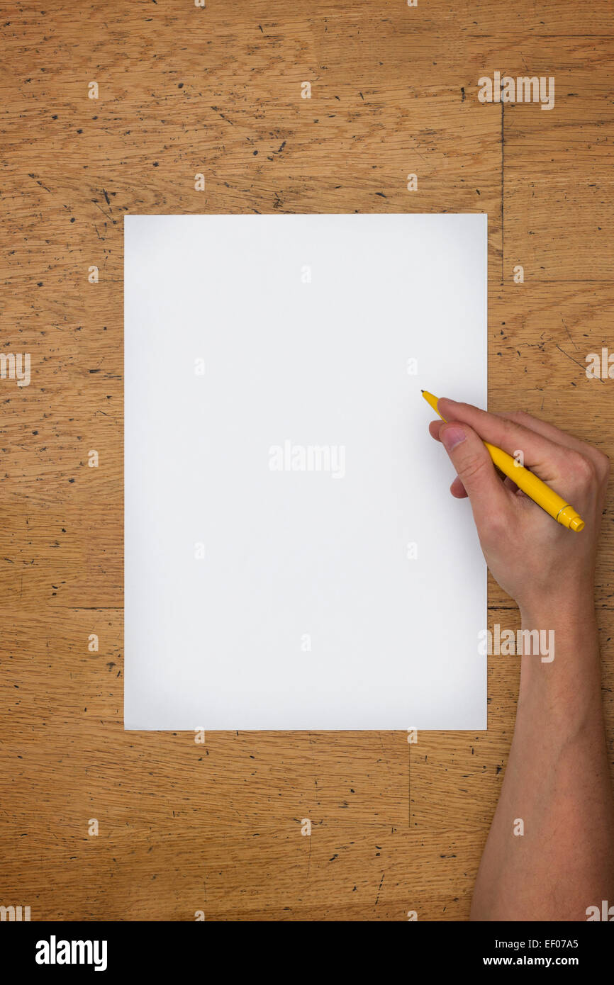Hand holding pen on a blank white paper sheet on a worn wooden table surface, viewed from above - Stock Image