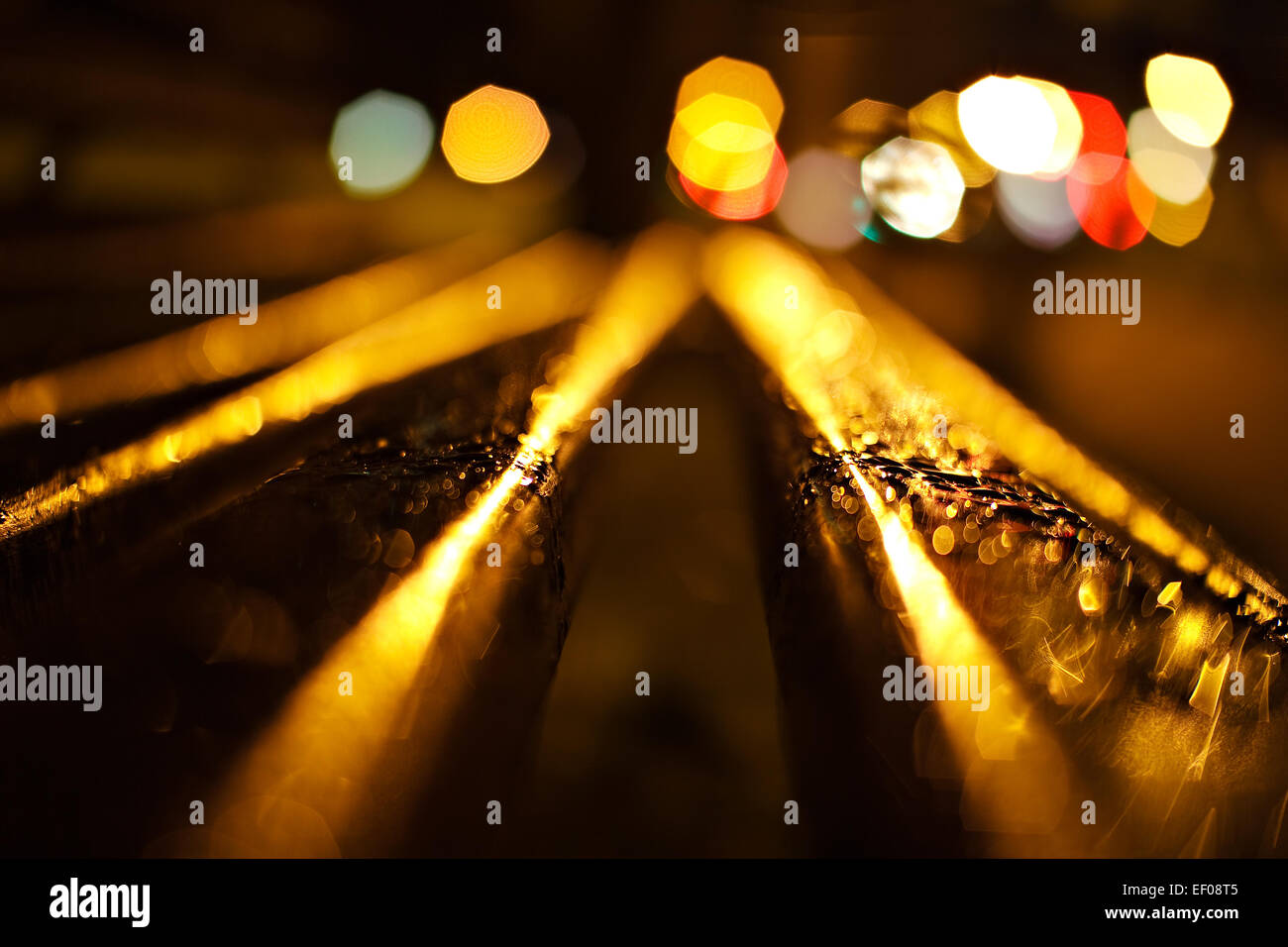 A park bench at night in the rain. - Stock Image