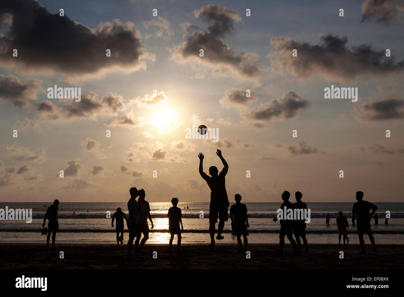 Young local boys playing football on a beach in Bali, Indonsesia Stock Photo