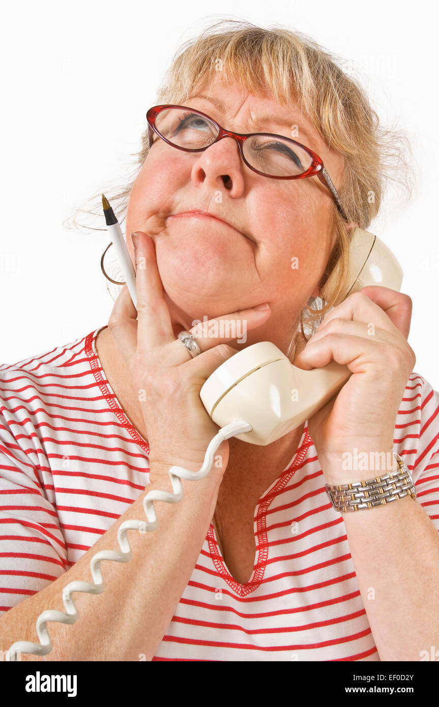 Woman Thinking While Listening To Someone On The Phone Stock Photo