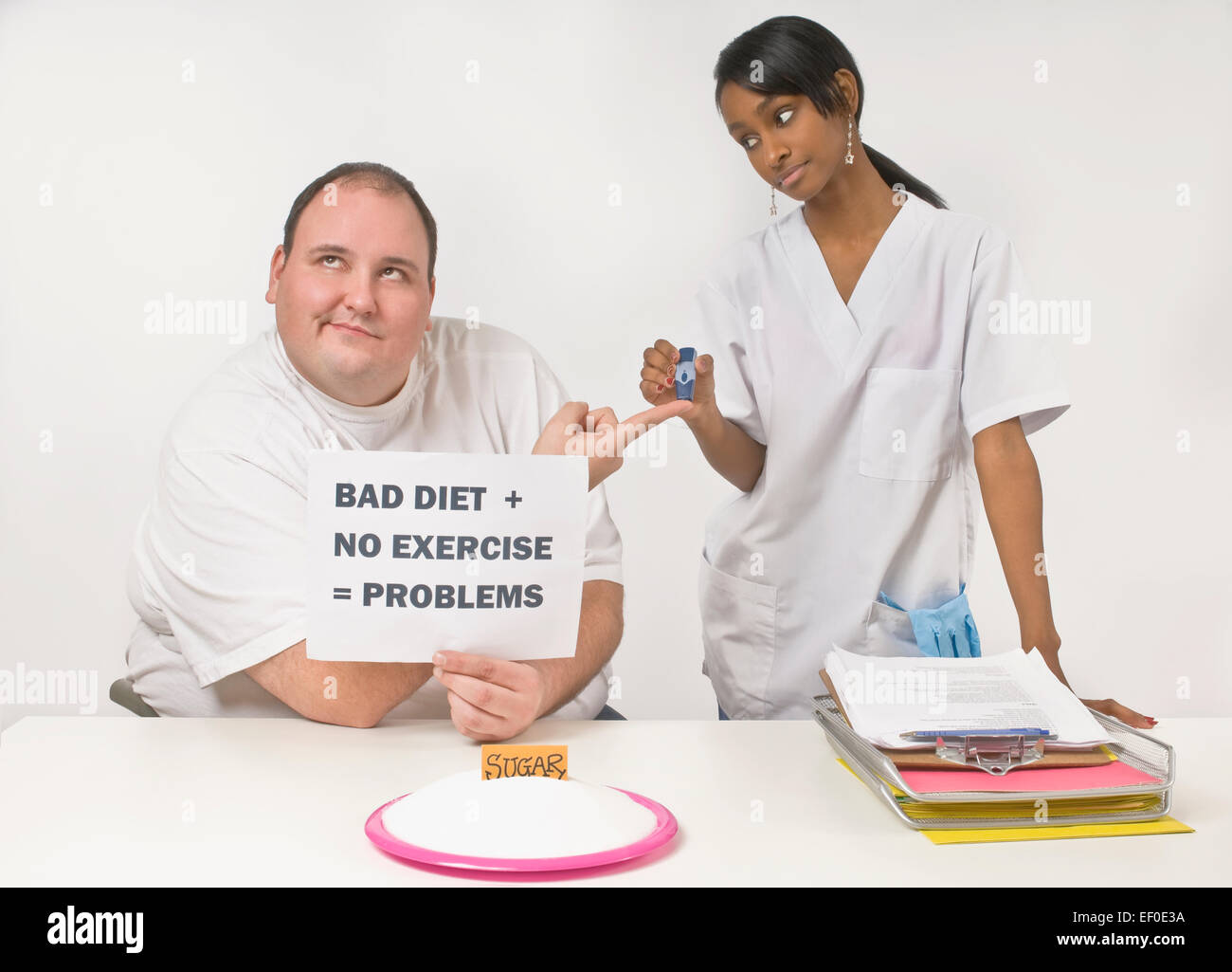 Nurse checking overweight man's blood glucose levels - Stock Image
