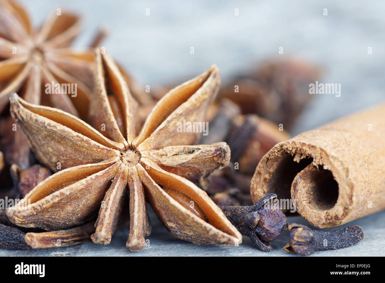 Anise star, cinnamon sticks, and cloves on old grey wood closeup - Stock Image