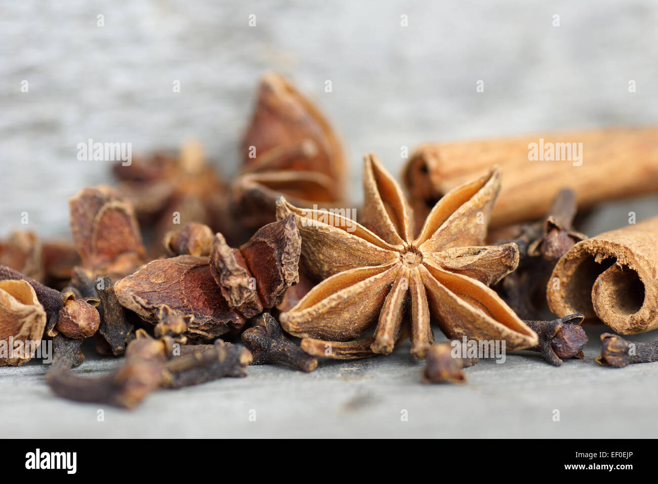 Anise star, cinnamon sticks, and cloves on old grey wood - Stock Image