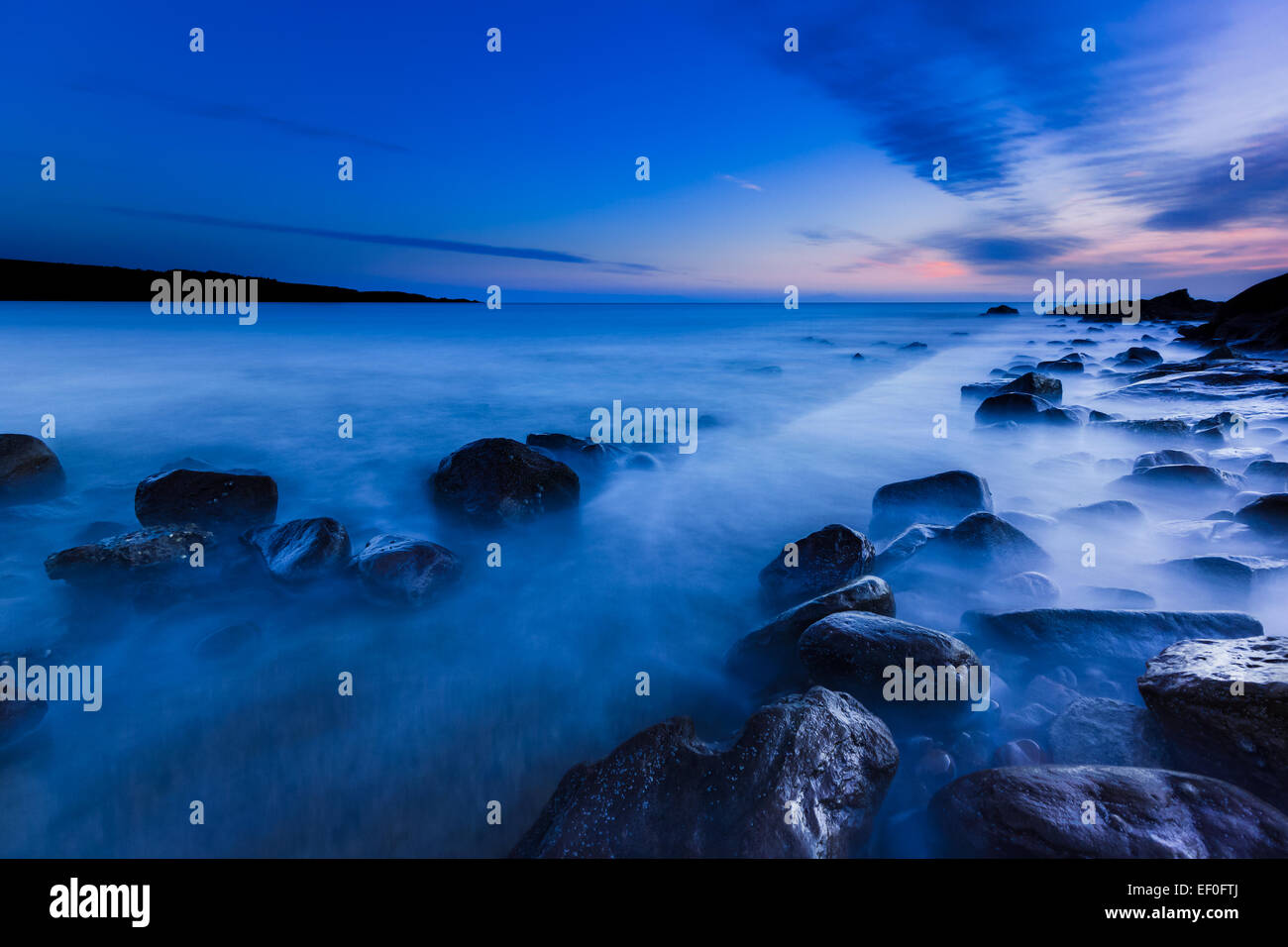 blue hour on a rocky shore - Stock Image