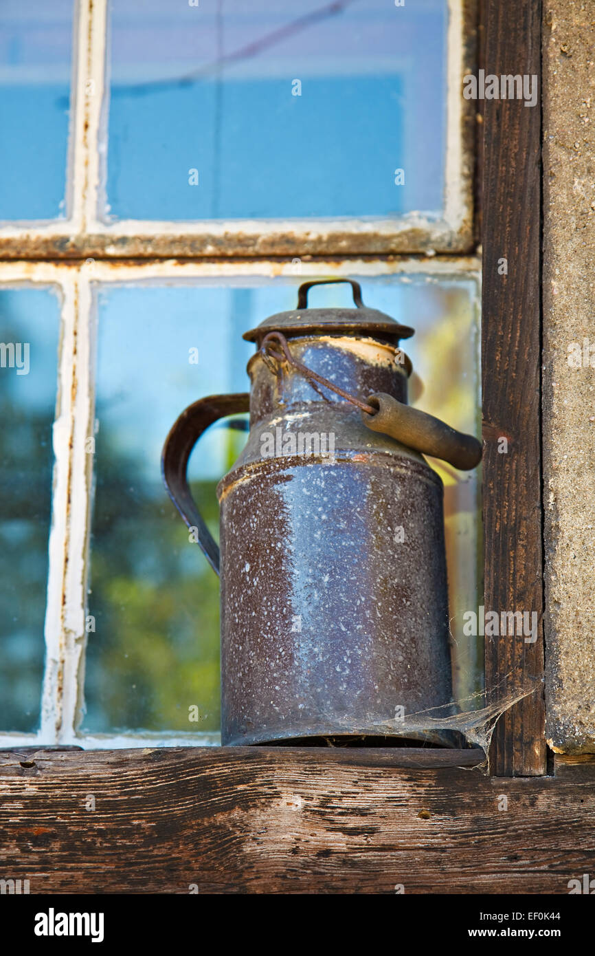 An old milk jug on a window sill. - Stock Image