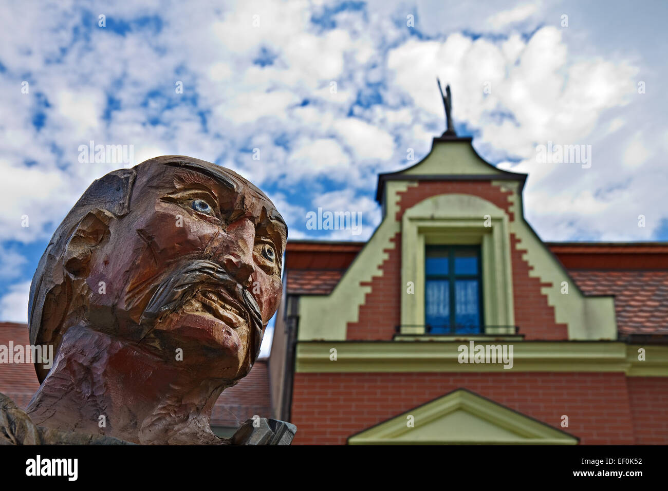 A wooden figure in front of a house gable. - Stock Image