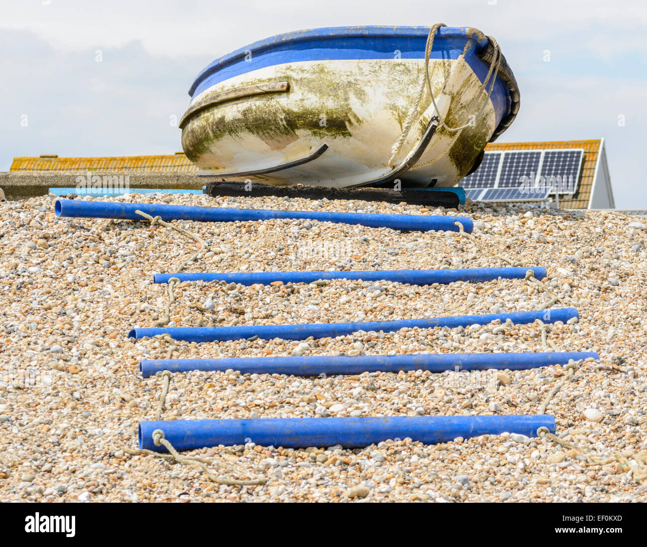Boat rollers and a boat on a shingle beach. - Stock Image
