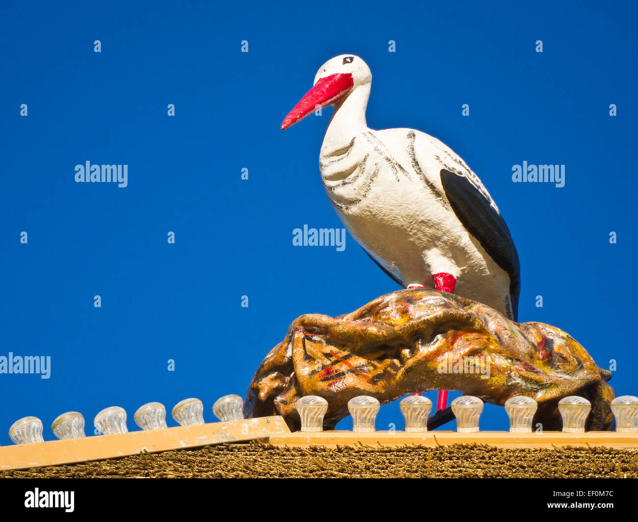 A stork figure on a roof. - Stock Image