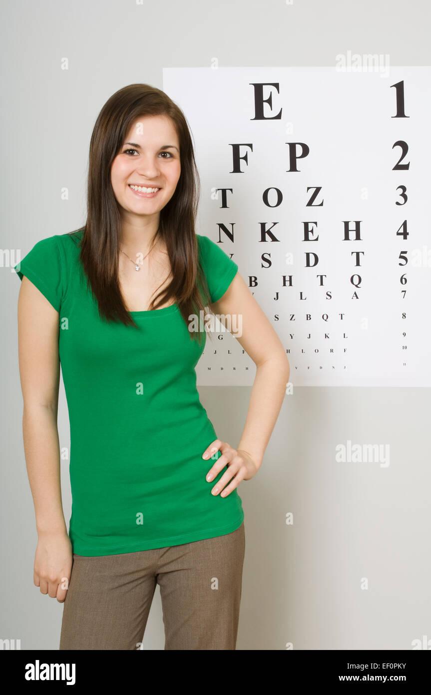 Woman standing beside eye chart - Stock Image