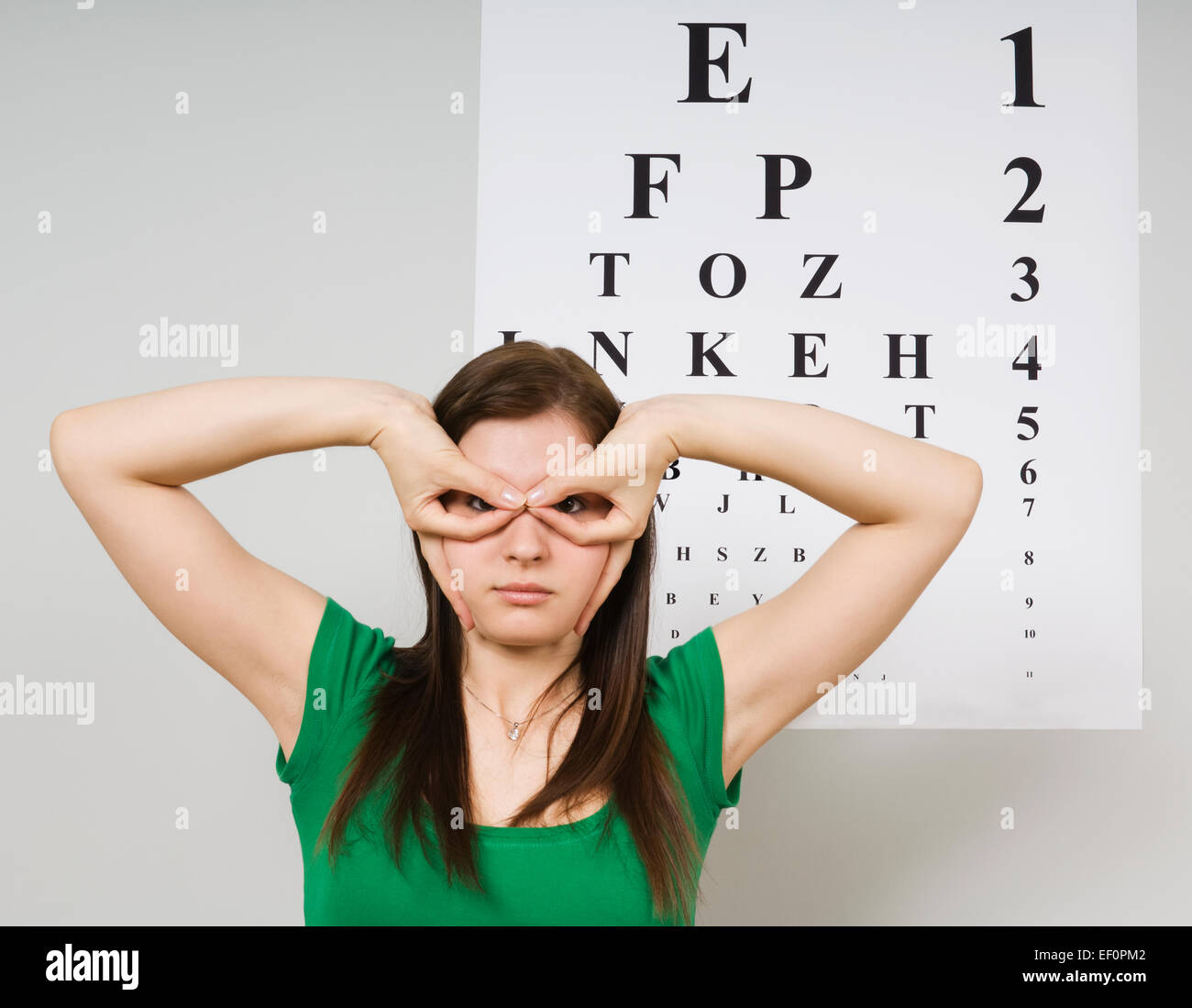 Woman standing in front of eye chart - Stock Image