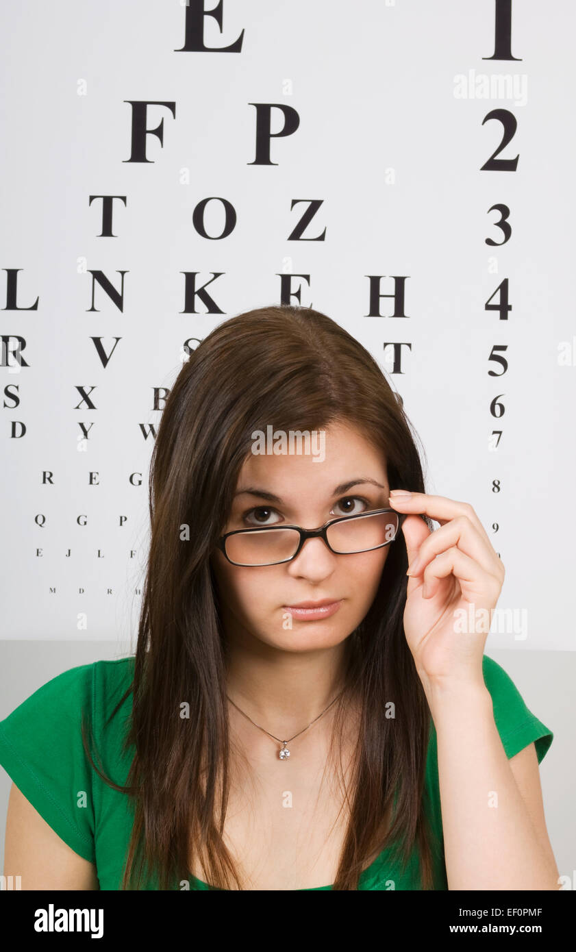 Woman sitting in front of eye chart - Stock Image