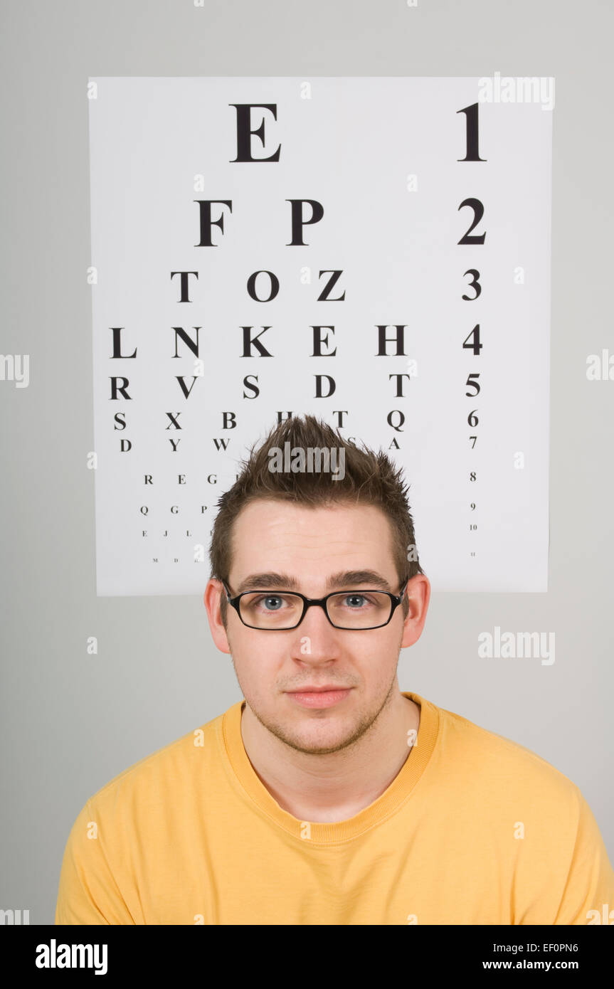 Man sitting in front of eye chart - Stock Image