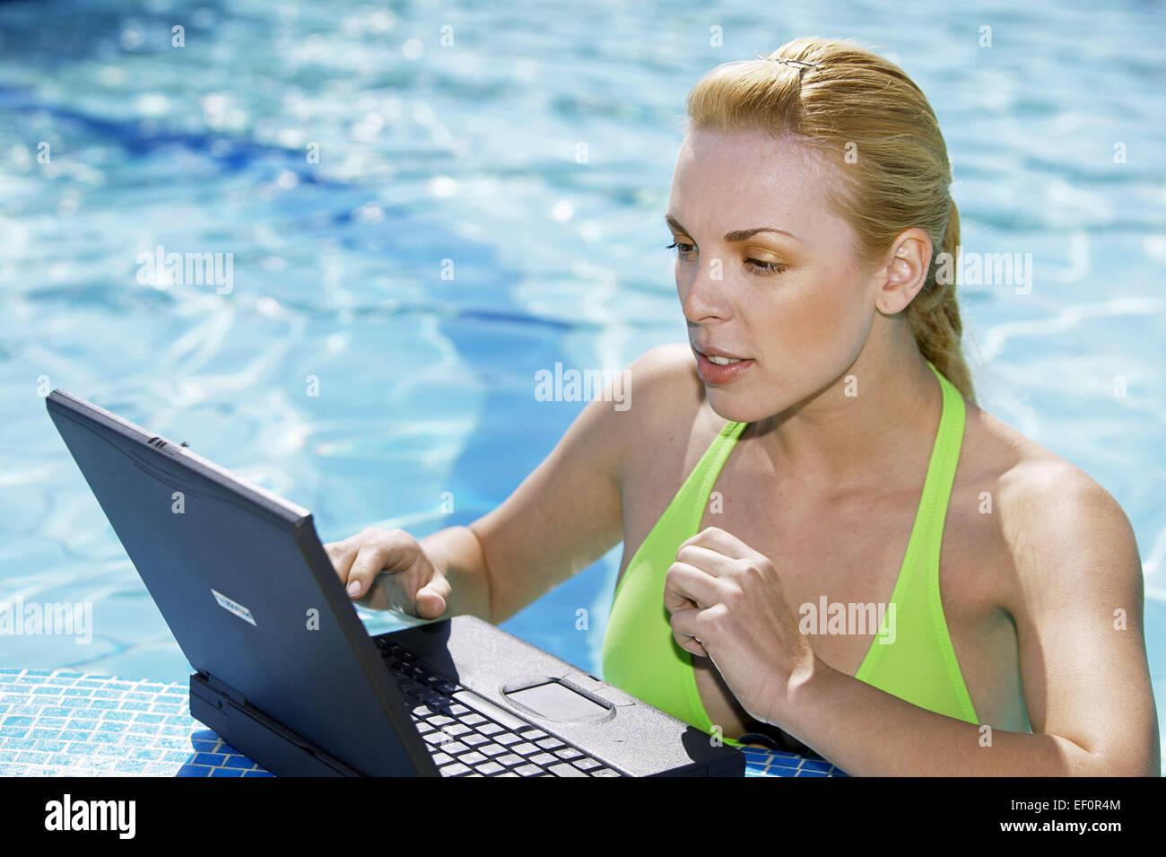 Pool Beckenrand Frau Jung Laptop Dateneingabe Swimmingpool Schwimmbecken Sommer Aussen Wasser Erfrischung Arbeit - Stock Image
