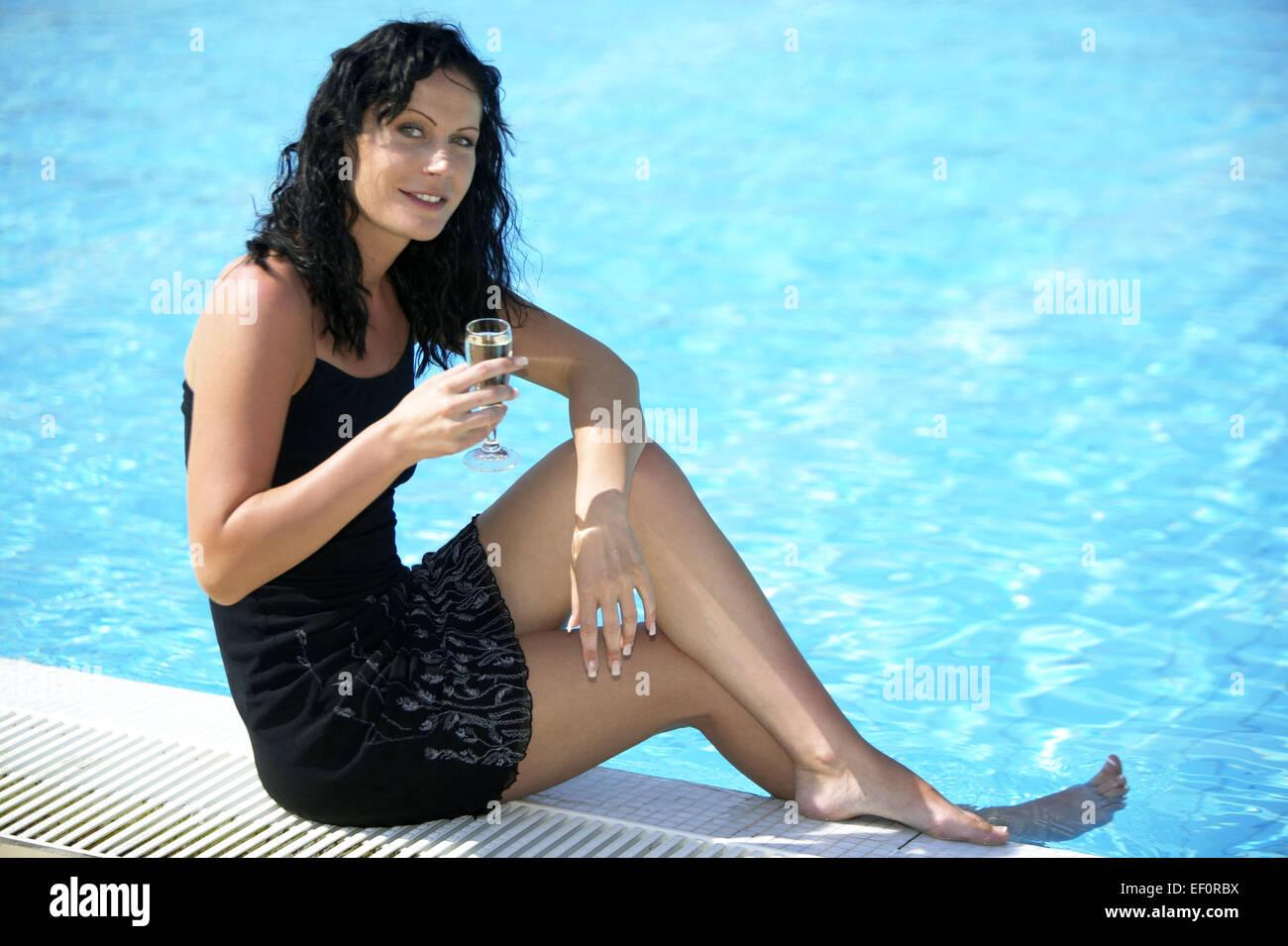 Frau Schwarzhaarig Pool Beckenrand Sitzen Jung Kleid Sommerkleid Barfuss Entspannt Gluecklich Trinken Sekt Champagner - Stock Image