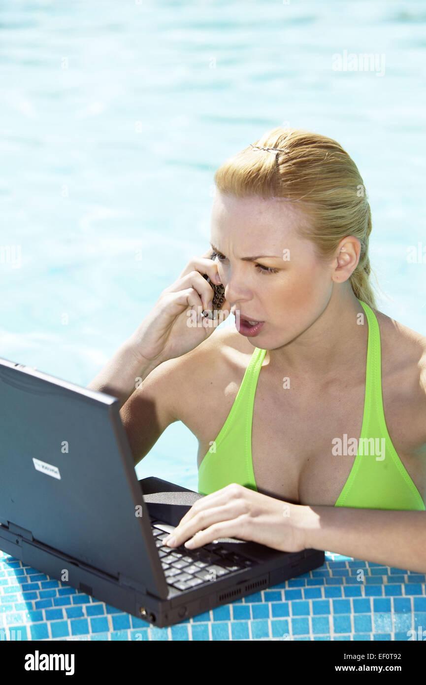 Pool Beckenrand Frau Jung Laptop Dateneingabe Telefonieren Handy Mobiltelefon Kommunikation Swimmingpool Schwimmbecken - Stock Image