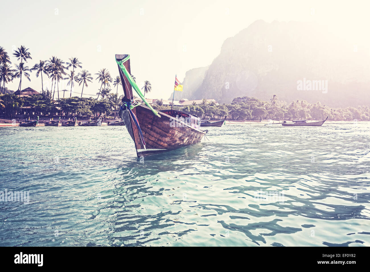 Retro filtered picture of boat and tropical island. - Stock Image
