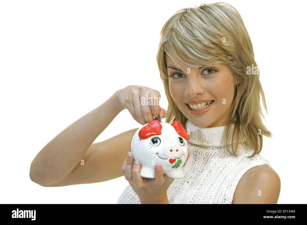 Frau, Sparschwein, halten, Geldstueck, einwerfen, Portrait, Frauenportrait, 20-30 Jahre, jung, blond, sparen, sparsam, - Stock Image
