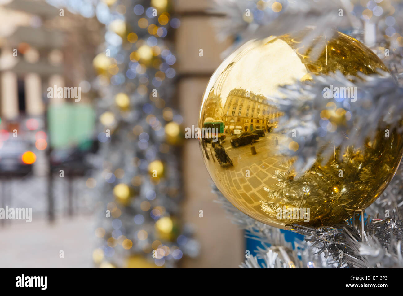 Golden shiny ball on Christmas decorated street in Paris, France - Stock Image