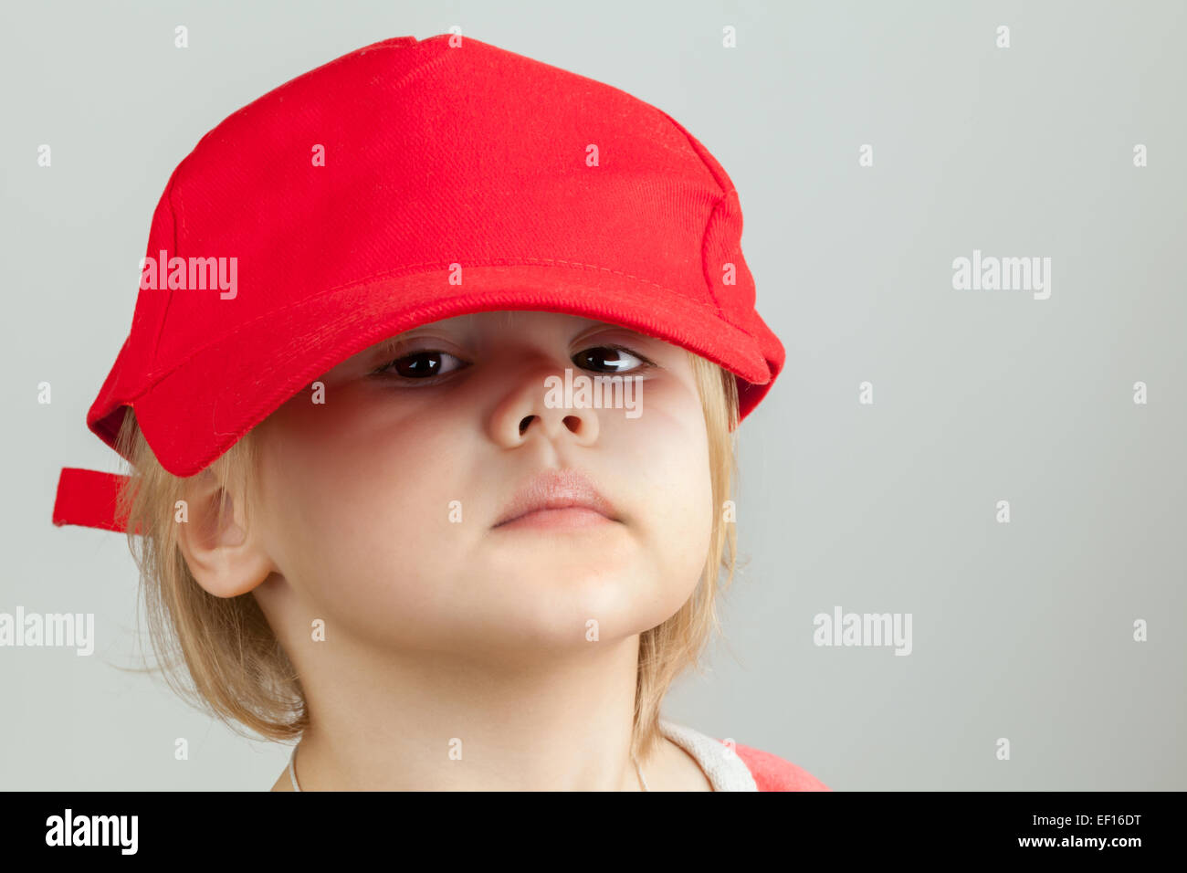 Studio portrait of funny baby girl in big red baseball cap over gray wall  background ef393283a7db