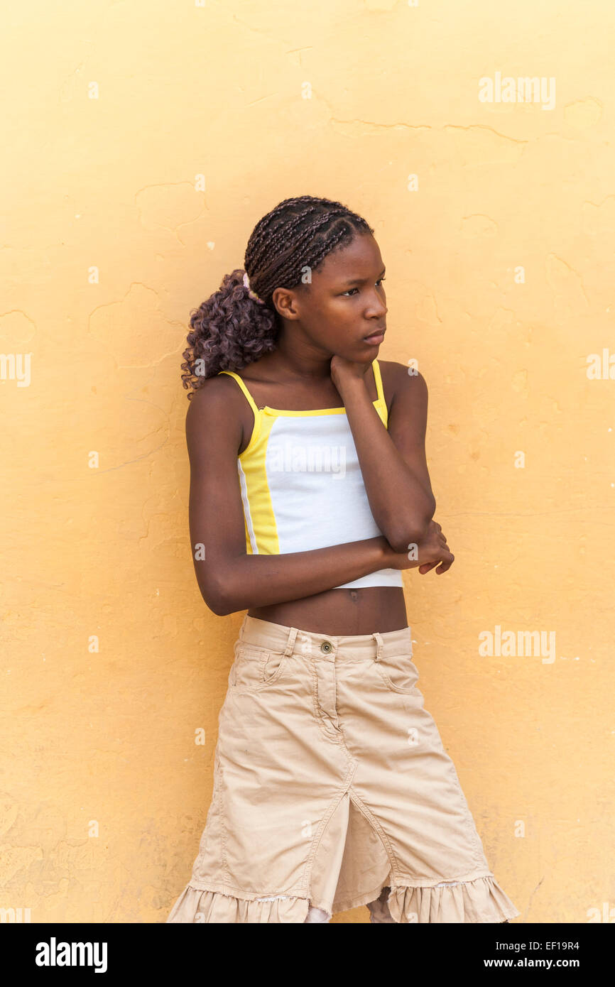 Thoughtful slim local young afro-Caribbean Cuban girl with braided hair leaning against a yellow wall in Trinidad, - Stock Image