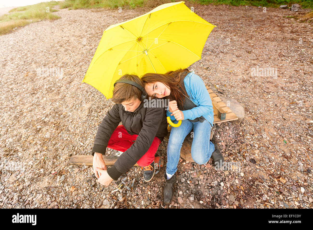 brother and sister with yellow umbrella sitting on a dirty beach Stock Photo