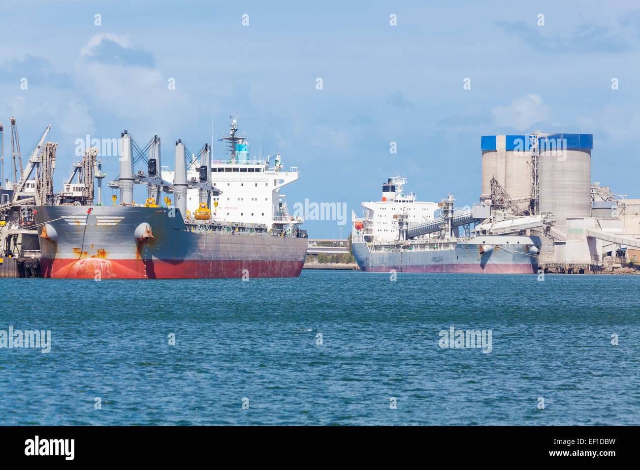 Cargo ships unloading at a port - Stock Image