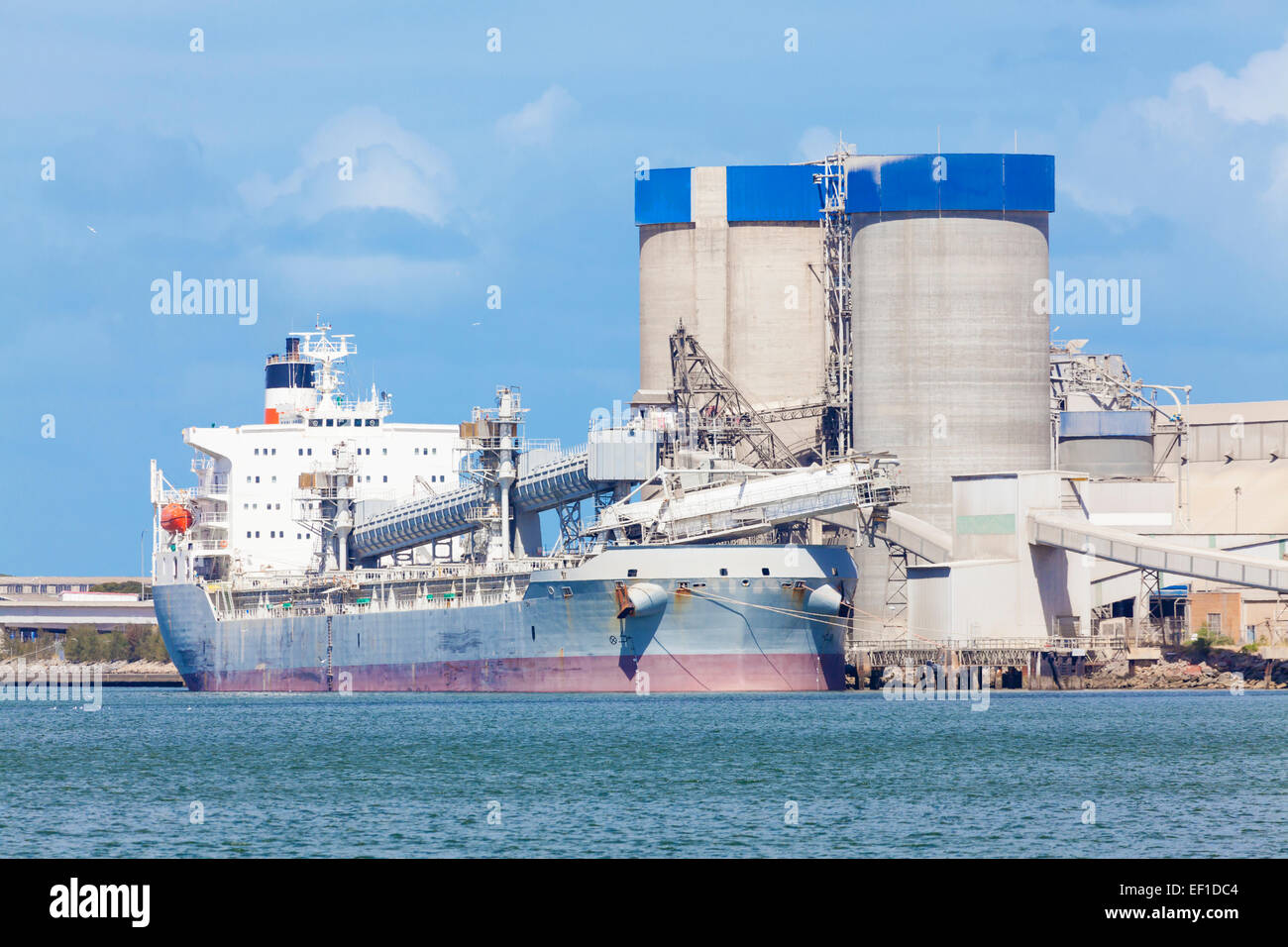 Cargo ship unloading at a cement plant - Stock Image