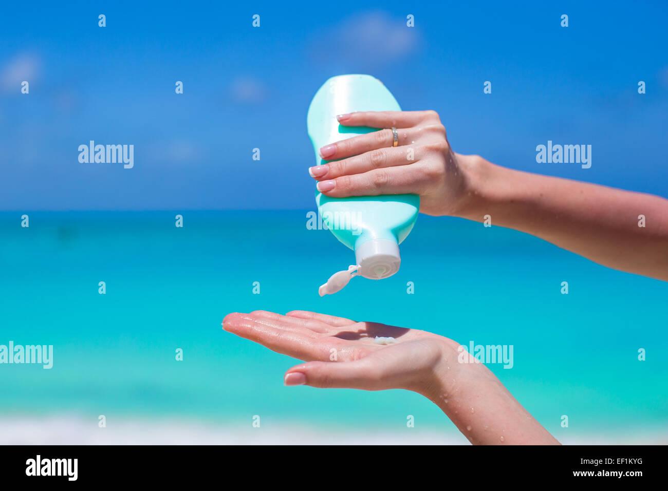 Closeup on female hand squeezing sun cream - Stock Image