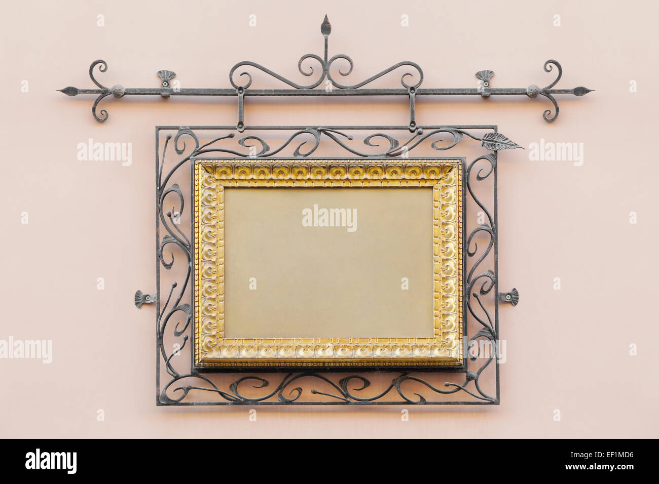 vintage frame decorated with wrought iron on the home wall of  house outdoors - Stock Image