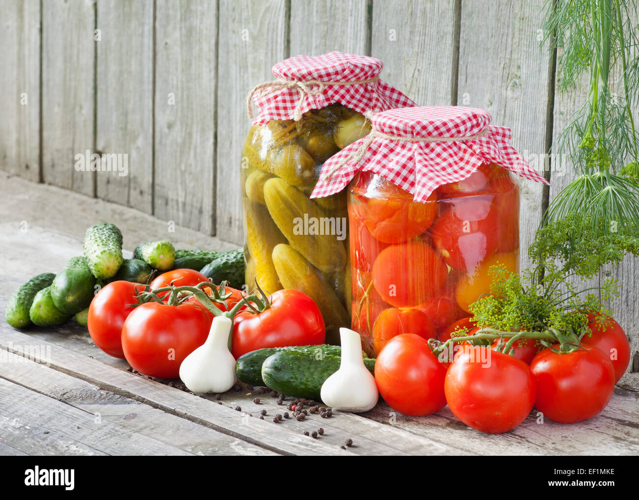 canned tomatoes and pickled cucumbers, homemade preserved vegetables - Stock Image