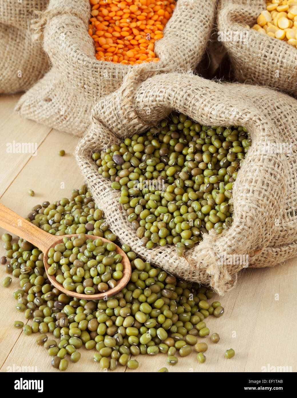 hessian bags with cereal grains: green mung closeup, red lentils and peas on wooden table - Stock Image