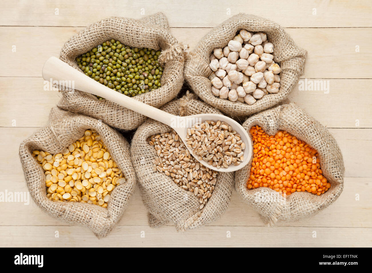 hessian bags with red lentils, peas, chick peas, wheat and green mung on wooden table - Stock Image