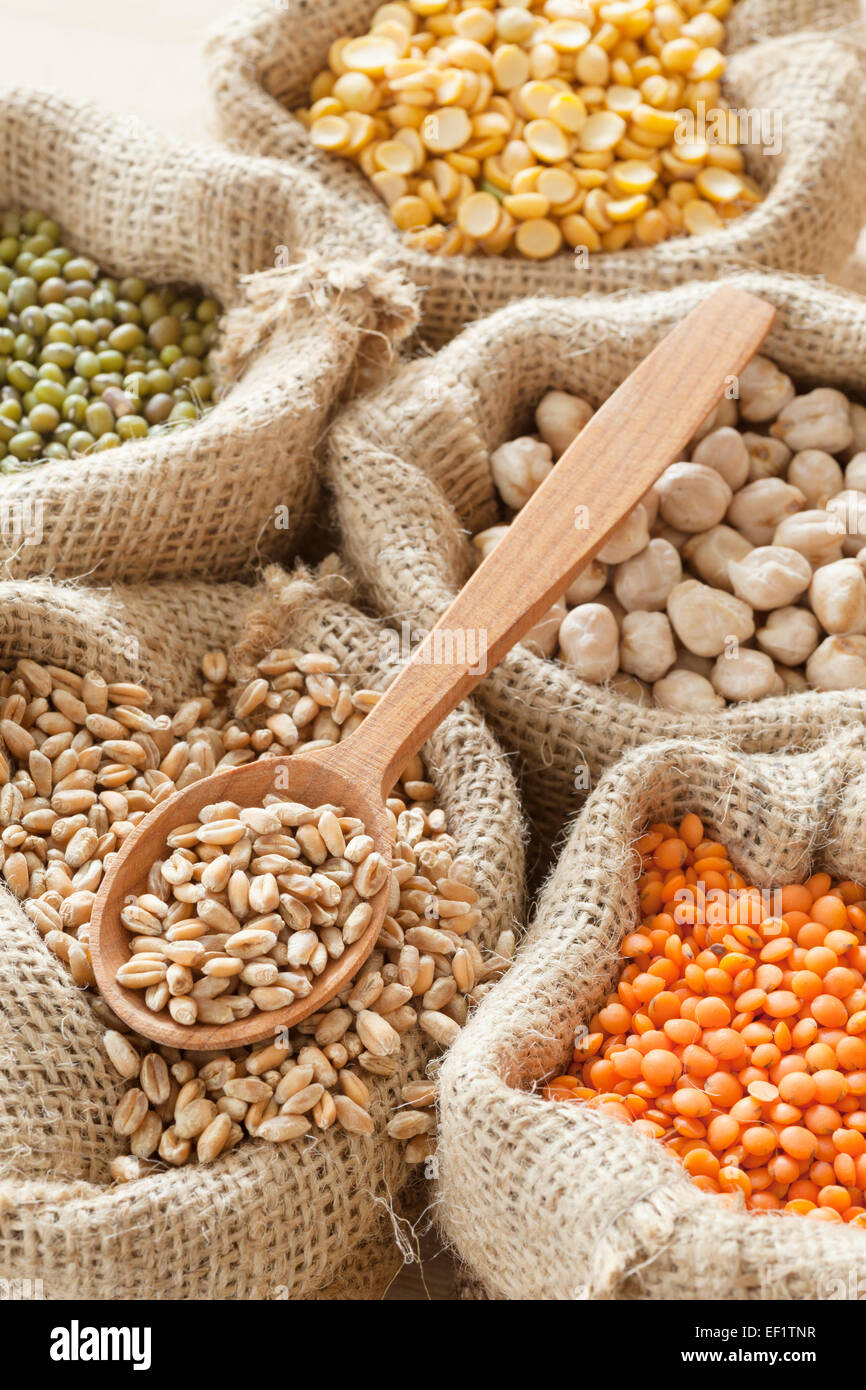 hessian bags with wheat,  peas, chick peas, red lentils and green mung, wooden spoon - Stock Image