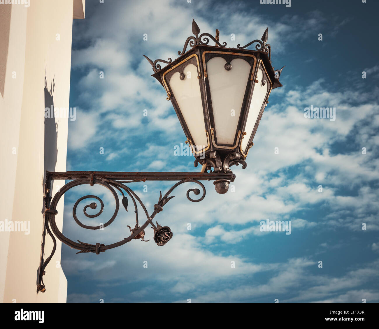 decorative  wall street lamp on blue sky background - Stock Image