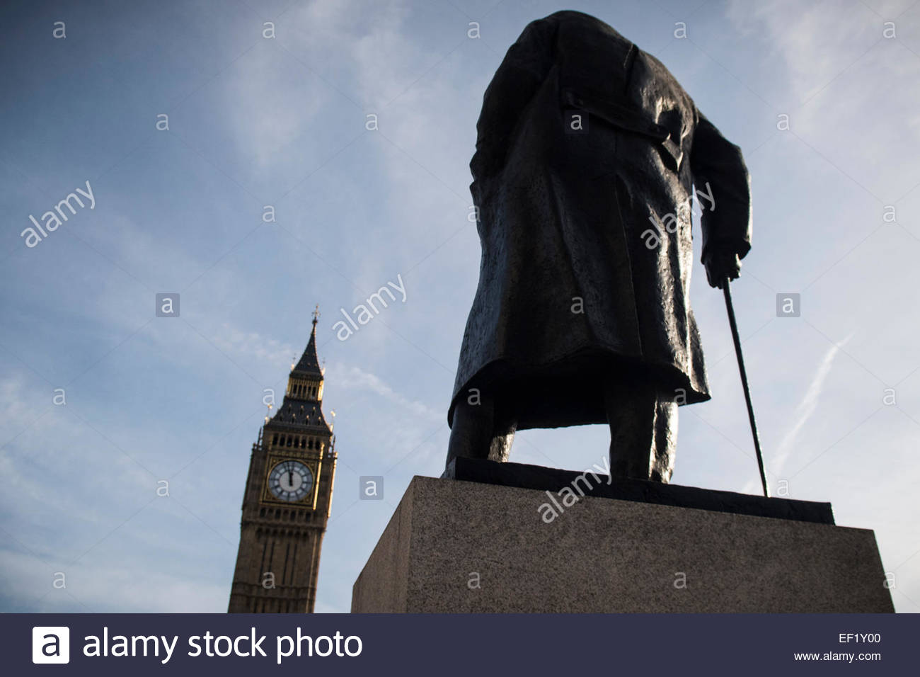 Bronze statue of Sir Winston Churchill, looming over Parliament Square to Big Ben, Westminster, London, UK. 24 January - Stock Image