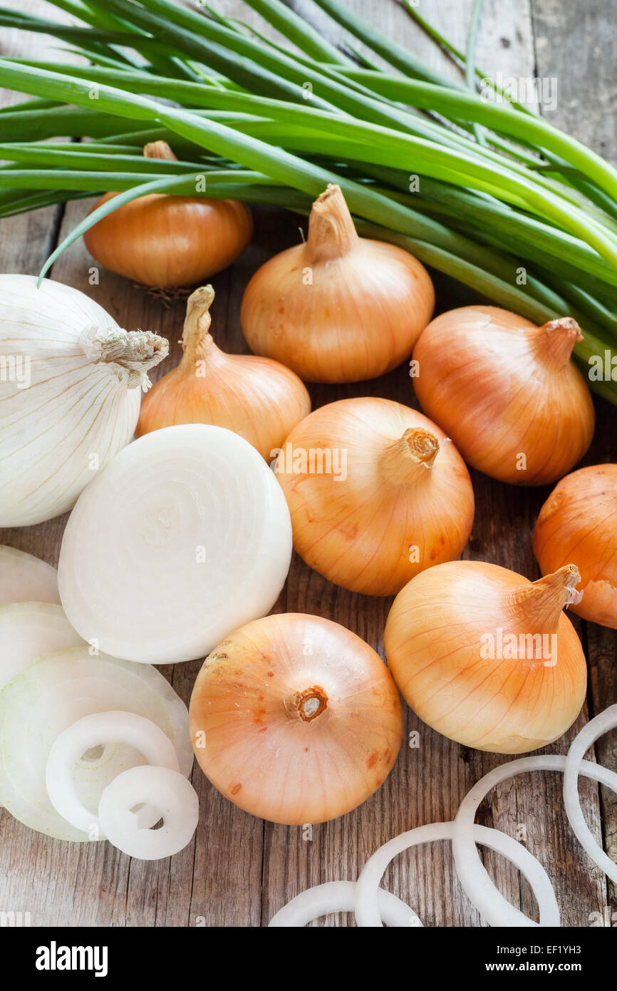 different onions on wooden rustic table - Stock Image