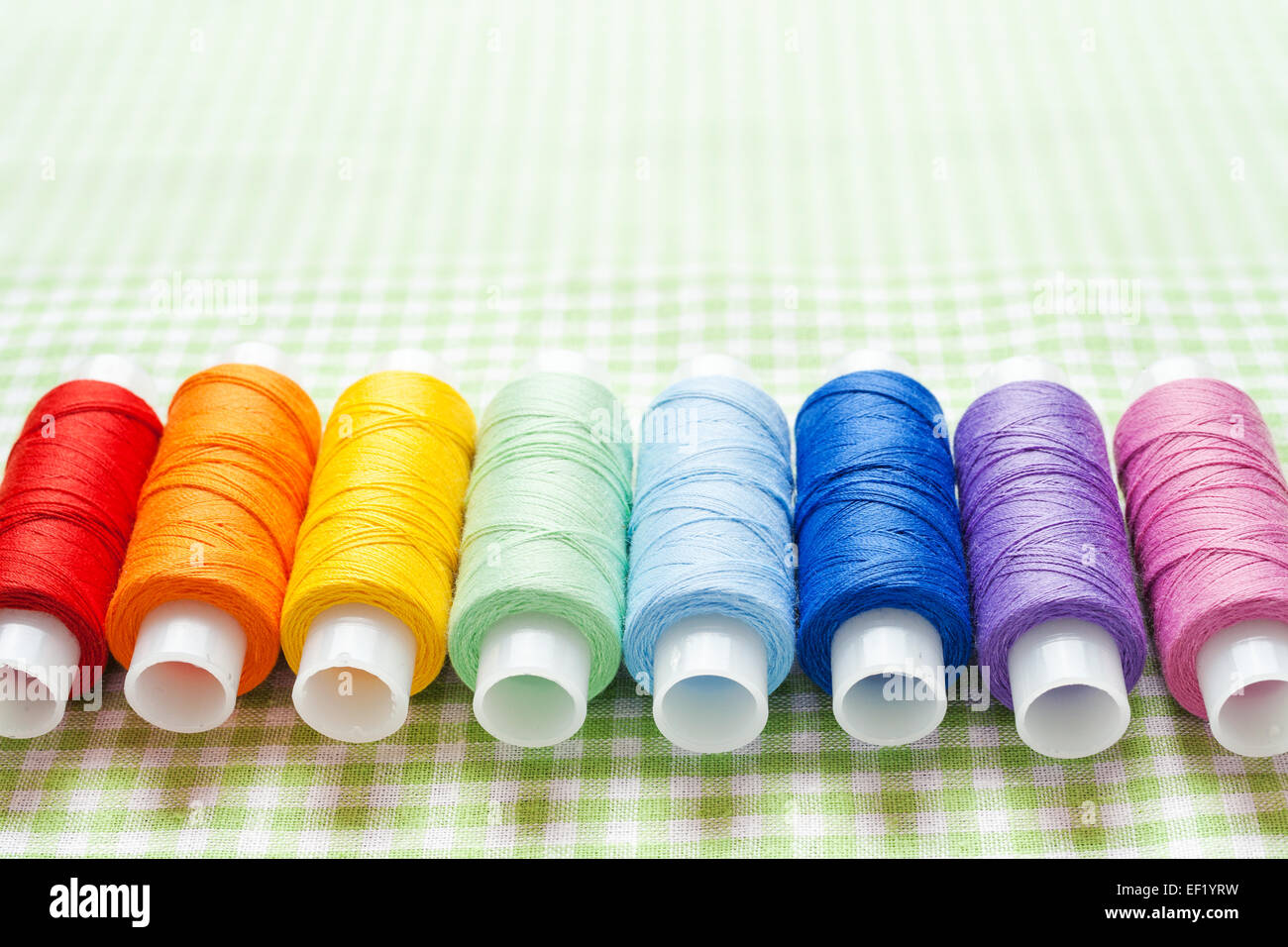 row of thread spools in rainbow colors, skein collection, top view - Stock Image