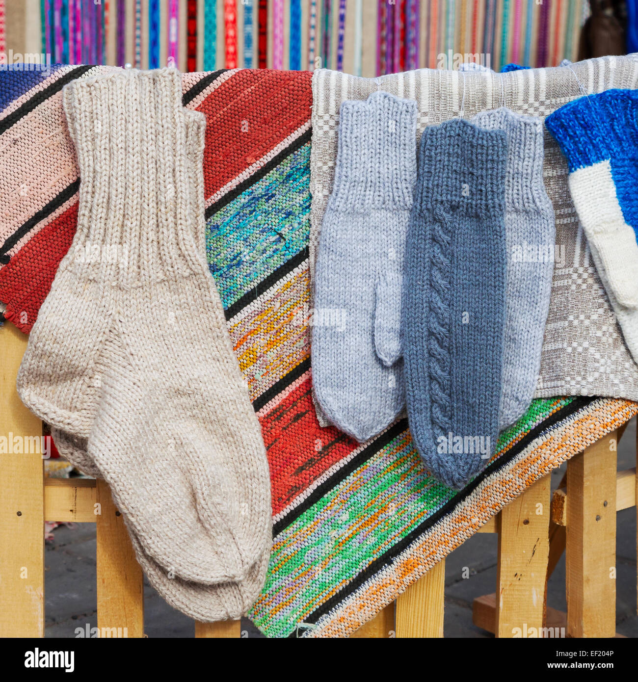 wool socks and mittens hanging on simple rustic cloth - Stock Image