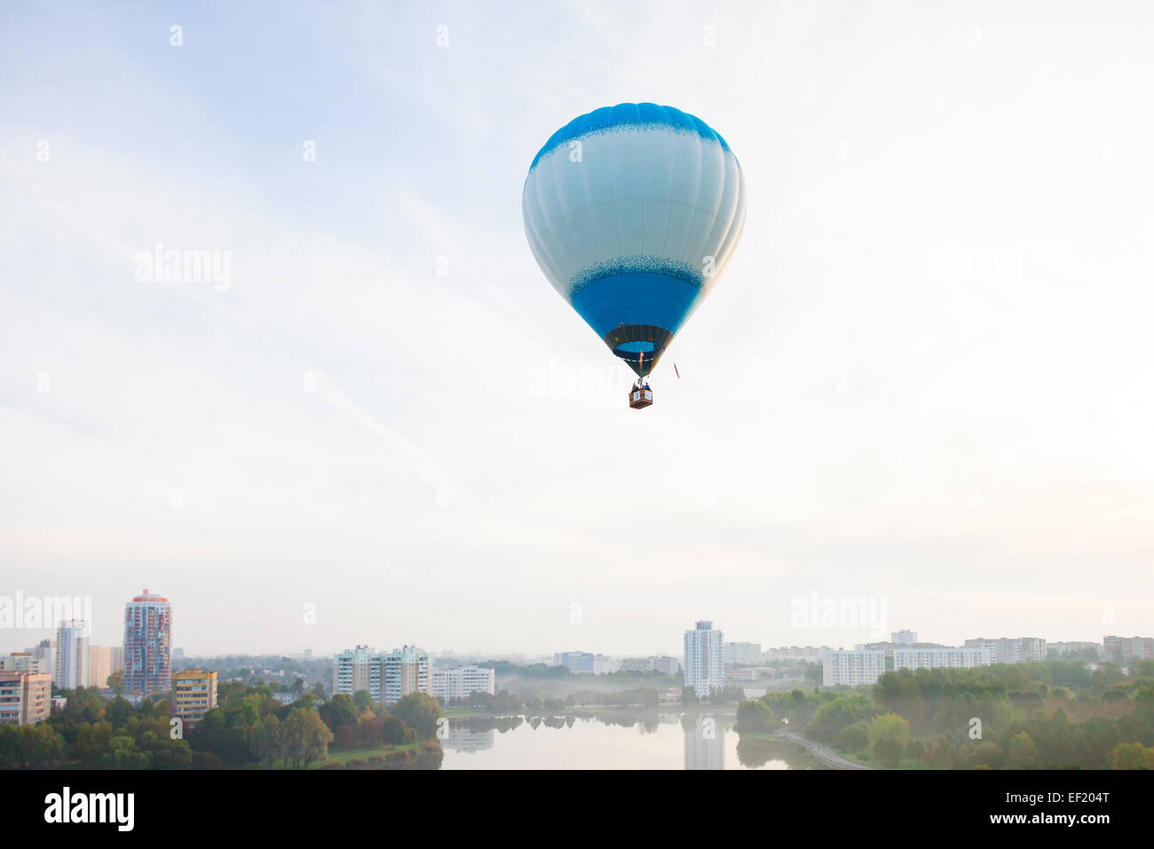 Hot air baloon flying over city - Stock Image